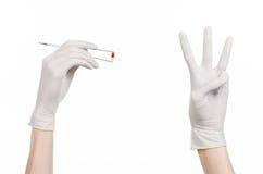 Farmakologi- och läkarundersökningtema: doktors hand i hållande pincett för en vithandske med den röda preventivpillerkapseln som Royaltyfri Fotografi