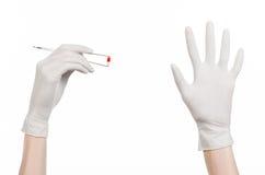 Farmakologia i Medyczny temat: lekarki ręka w bielu mienia rękawiczkowych pincetach z czerwoną pigułki kapsułą odizolowywającą na Fotografia Royalty Free