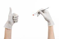 Farmakologia i Medyczny temat: lekarki ręka w bielu mienia rękawiczkowych pincetach z czerwoną pigułki kapsułą odizolowywającą na Obrazy Stock