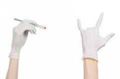 Farmakologia i Medyczny temat: lekarki ręka w bielu mienia rękawiczkowych pincetach z czerwoną pigułki kapsułą odizolowywającą na Zdjęcia Stock