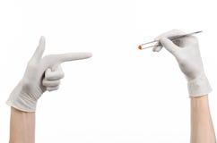 Farmakologia i Medyczny temat: lekarki ręka w bielu mienia rękawiczkowych pincetach z czerwoną pigułki kapsułą odizolowywającą na Obraz Royalty Free