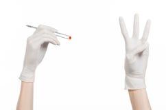 Farmakologia i Medyczny temat: lekarki ręka w bielu mienia rękawiczkowych pincetach z czerwoną pigułki kapsułą odizolowywającą na Zdjęcia Royalty Free