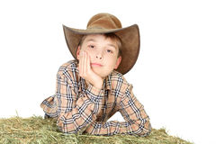 Farmboy die op hooibaal leunt Stock Foto's