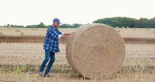 Farmer που αγωνίζεται κυλώντας το δέμα σανού στο αγρόκτημα φιλμ μικρού μήκους