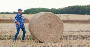 Farmer που αγωνίζεται κυλώντας το δέμα σανού στο αγρόκτημα απόθεμα βίντεο