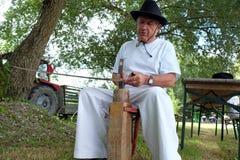 Farmer που ακονίζει το δρεπάνι του στοκ εικόνα
