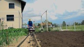 Farmer που αναποδογυρίζει το ανώτερο στρώμα του χώματος με τον καλλιεργητή του απόθεμα βίντεο