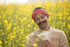 Farmer που κρατά τις ινδικές σημειώσεις ρουπίων στον τομέα στοκ φωτογραφία