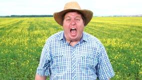 Farmer που στέκεται στον τομέα και που κραυγάζει στη φρίκη ή το κακό, στο καπέλο μια ηλιόλουστη ημέρα φιλμ μικρού μήκους