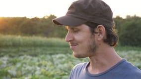 Farmer που στέκεται στον τομέα του οργανικού αγροκτήματος, της κατανάλωσης του φρέσκου ώριμου αγγουριού και του χαμόγελου φιλμ μικρού μήκους