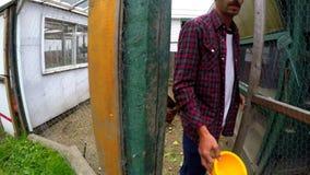 Farmer που ταΐζει την κότα στο σπίτι κοτών 4k απόθεμα βίντεο