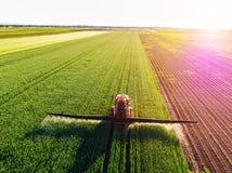 Farmer που ψεκάζει τον πράσινο τομέα σίτου στοκ φωτογραφία με δικαίωμα ελεύθερης χρήσης