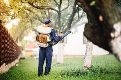 Farmer που ψεκάζει το φυτοφάρμακο και το ζιζανιοκτόνο στον αγροτικό κήπο στοκ φωτογραφία με δικαίωμα ελεύθερης χρήσης