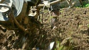 Farmer χρησιμοποιώντας τον καλλιεργητή μηχανών mart για το όργωμα του χώματος φιλμ μικρού μήκους