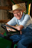 Farmer. A farmer sitting on his tractor in the barn royalty free stock photography