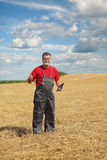 Farmer or agronomist inspect in wheat field after harvest Stock Images
