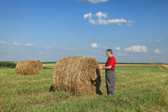 Farmer and bale of hay in field Stock Images