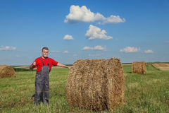 Farmer and bale of hay in field Royalty Free Stock Photos