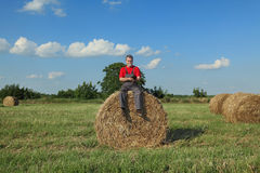 Farmer and bale of hay in field Royalty Free Stock Images
