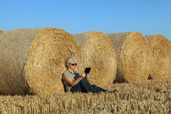 Farmer and bale of straw in field Stock Photography