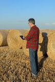 Farmer and bale of straw in field after harvest Royalty Free Stock Image