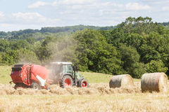 Farmer baling dried grass for hay with a tractor and baler, two. Round hay bales at the side in a rural hilltop pasture stock images