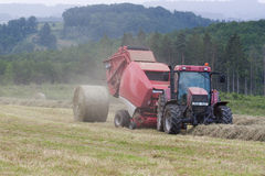 Farmer baling hay in a misty mountain pasture Royalty Free Stock Images