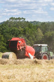 Farmer baling hay with a round   baler Royalty Free Stock Images