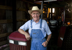 Farmer in the Barn. A farmer standing in front of his tractor in the barn Royalty Free Stock Photo