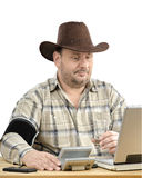 Farmer with blood pressure gauge looking at laptop Stock Images