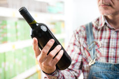 Farmer buying wine at supermarket Royalty Free Stock Image
