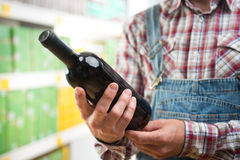 Farmer buying wine at supermarket Stock Images