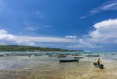 Seaweed farmer carrying baskets of algae at Nusa Lembongan, Bali. FArmer carrying daily algae harvest with boats of seaweed farmers and crystal clear waters of Stock Image