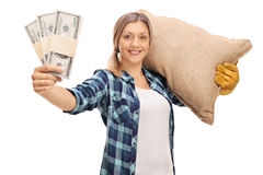 Farmer carrying a sack and holding money stacks Stock Image