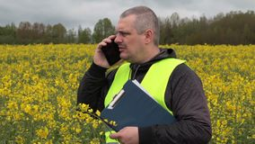 Farmer with cell phone near yellow rape field stock video footage