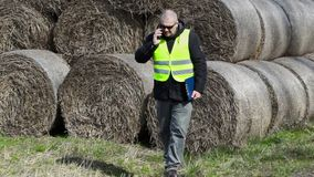 Farmer checking hay bales and talking on smartphone stock video