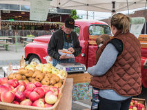 Farmer checks accounts for customer at Farmers Market, Corvallis Stock Photo