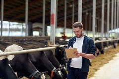 Farmer with clipboard and cows in cowshed on farm Stock Photos