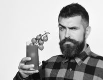 Farmer with confused face offers fresh juice made of tomatoes. Farmer with confused face offers fresh juice made of cherry tomatoes. Man with beard holds glass royalty free stock photography