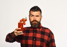 Farmer with confused face shows bunch of cherry tomatoes. Farming and autumn concept. Man with beard holds glass of tomato juice with berries isolated on white royalty free stock photography