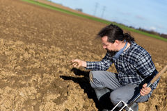 Farmer controlling the ground of his field Royalty Free Stock Images