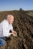 Farmer cupping soil in ploughed field with tractor and plough in background Stock Photos