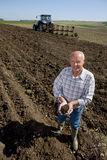 Farmer cupping soil in ploughed field with tractor and plough in background Stock Photography