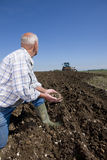 Farmer cupping soil and watching tractor ploughing field Stock Image