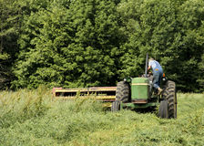Farmer cutting hay. Farmer getting on his tractor to cut a hay field Royalty Free Stock Photo