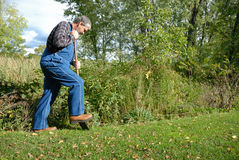 Farmer digging. Bearded farmer, wearing bib overalls & plaid shirt digging in meadow royalty free stock photo