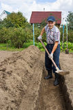 Farmer digging the earth to build a deep bed of Stock Photos