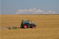 a blue tractor on a harvested grain field stock image