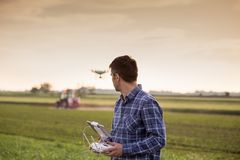 Farmer driving drone above field stock photos
