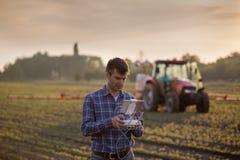 Farmer driving drone above field stock photo